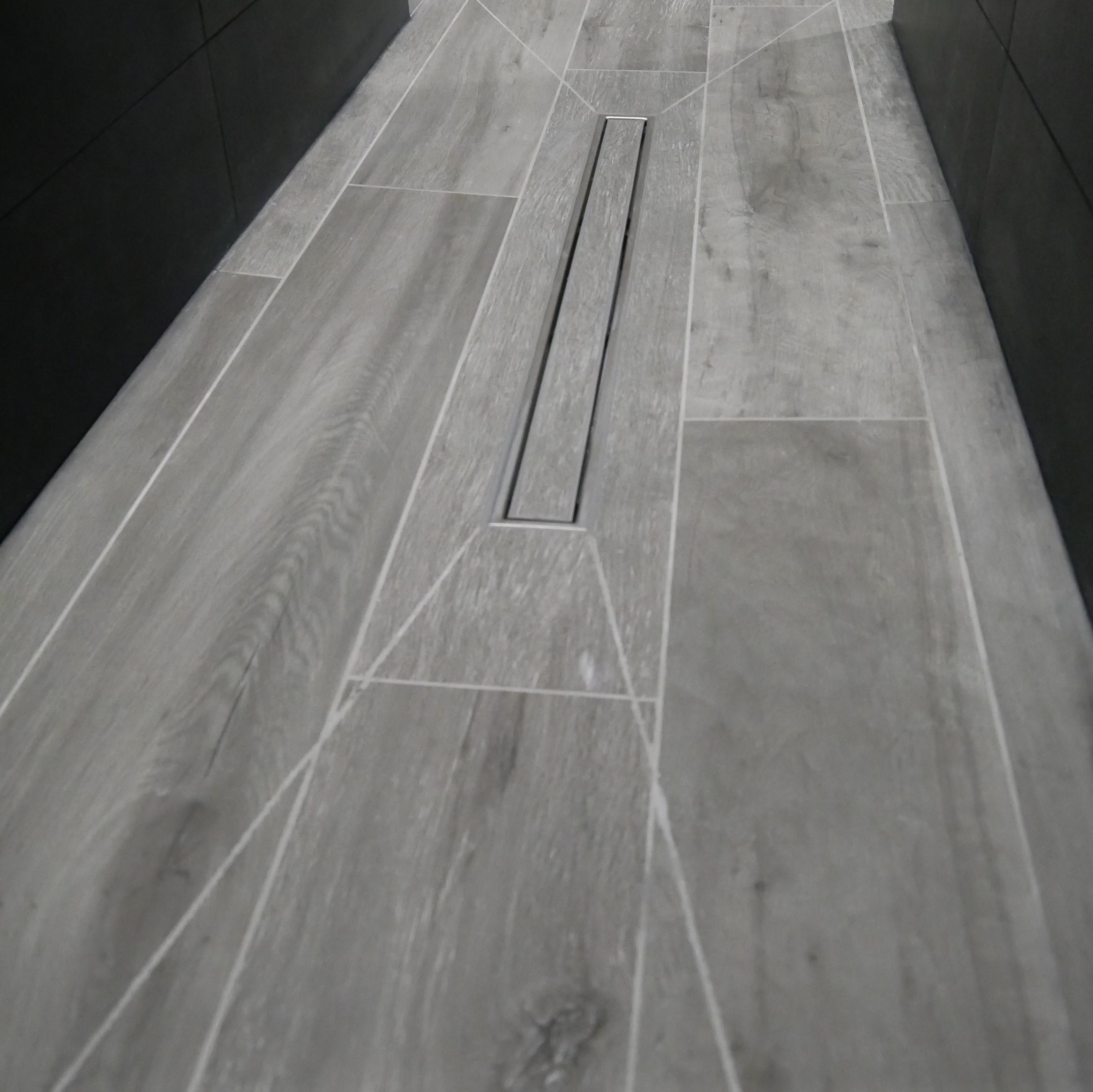 Magnifique douche à l'italienne design et morderne en carrelage imitation parquet avec une pose d'un caniveaux de douche carrelé BOSSARD assure votre confort au quotidien BOSSARD à Moncoutant mais intervient dans le 79,85,49 à BRESSUIRE CERIZAY MAULEON SECONDIGNY PARTHENAY CHICE CLESSE BOISME LA CHAPELLE SAINT LAURENT PUGNY LE BREUIL BERNARD AGGLO2B LARGEASSE NEUVY BOUIN LA FORET SUR SEVRE LA RONDE SAINT MARSAULT L ABSIE LE BUSSEAU SAINT PIERRE DU CHEMIN LA CHATAIGNERAIE LE BREUIL BARRE LE BUSSEAU COULONGES SUR L AUTIZE BEAULIEUR NOIRTERRE SAINT SAUVEUR TERVES CHANTELOUP COURLAY PUGNY LE BREUIL BERNARD SAINT JOUIN DE MILLY LES MOUTIERS SOUS CHANTEMERLE LE PIN LA PETITE BOISSIERE
